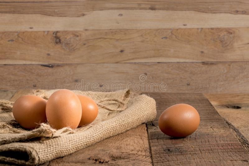 Freshly laid organic eggs on wooden bench. Easter background with brown organic eggs arranged on burlap sack on rustic wooden table stock images