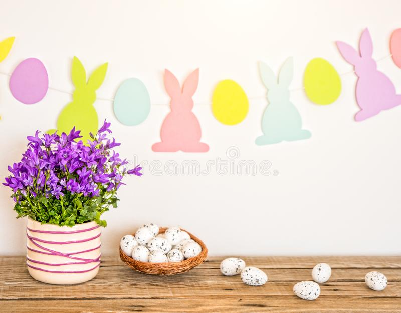 Easter background with bunnies garland, spring flowers and eggs on wood table stock image