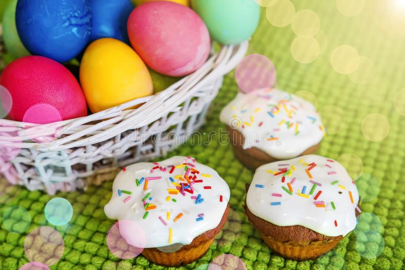 Easter background. Colorful Easter eggs and sweet cupcakes on a green background. Spring Christian religious holiday royalty free stock photo