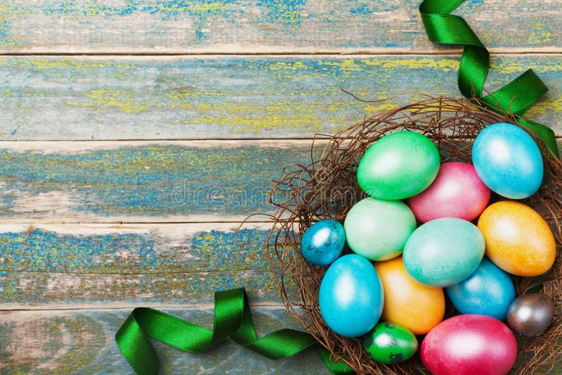 Easter background with colorful eggs in nest decorated with green satin ribbon. Copy space for greeting text. Top view. stock image