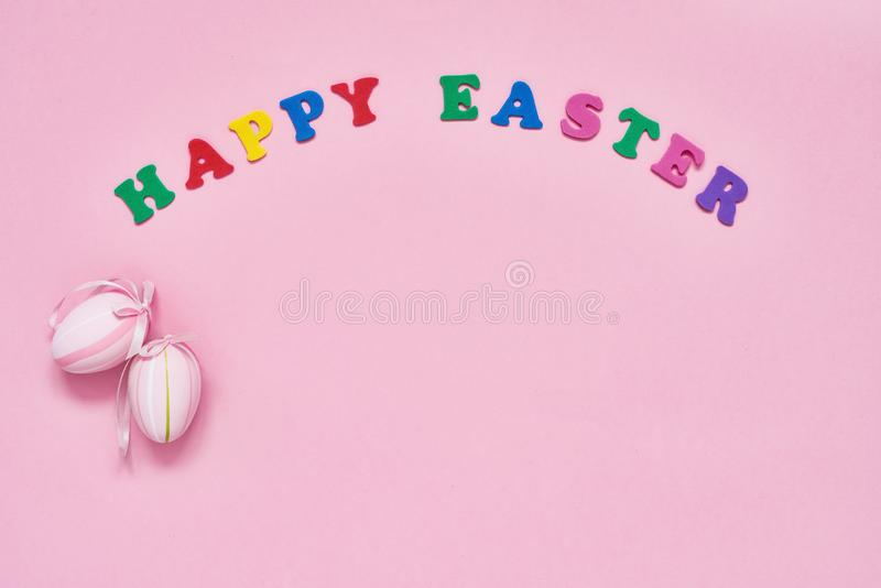 Easter background. Easter decoration and colorful letters forming words HAPPY EASTER on pink background. Copy space for your text royalty free stock photos