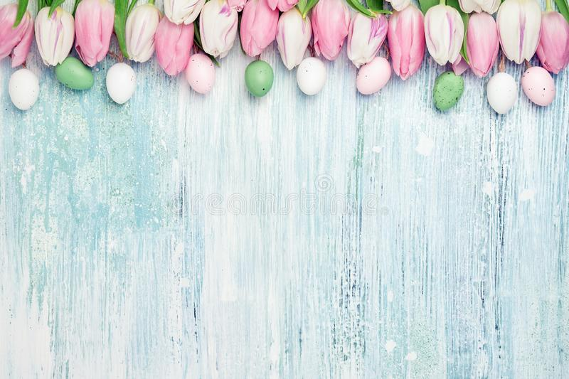 Easter background. Decorative Easter eggs and pink tulips border on wooden background. Holiday card, copy space. Easter concept royalty free stock photo