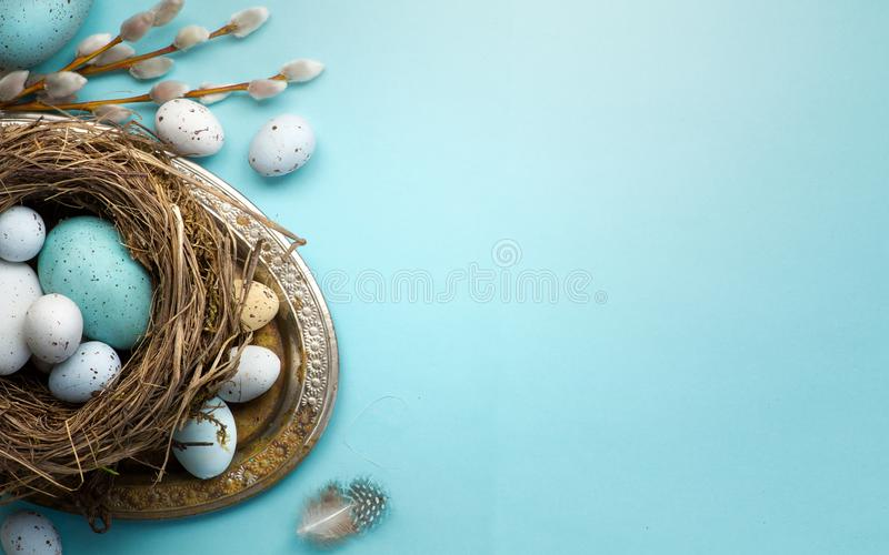 Easter background with Easter eggs and spring flowers on blue t. Art Easter background with Easter eggs and spring flowers on blue table royalty free stock images