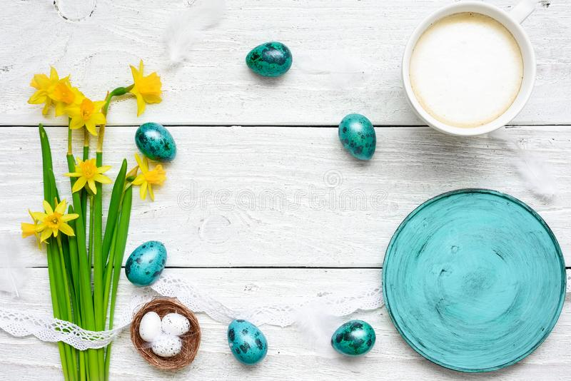 Easter background with easter eggs, spring flowers, cup of cappuccino and and empty blue plate royalty free stock photos
