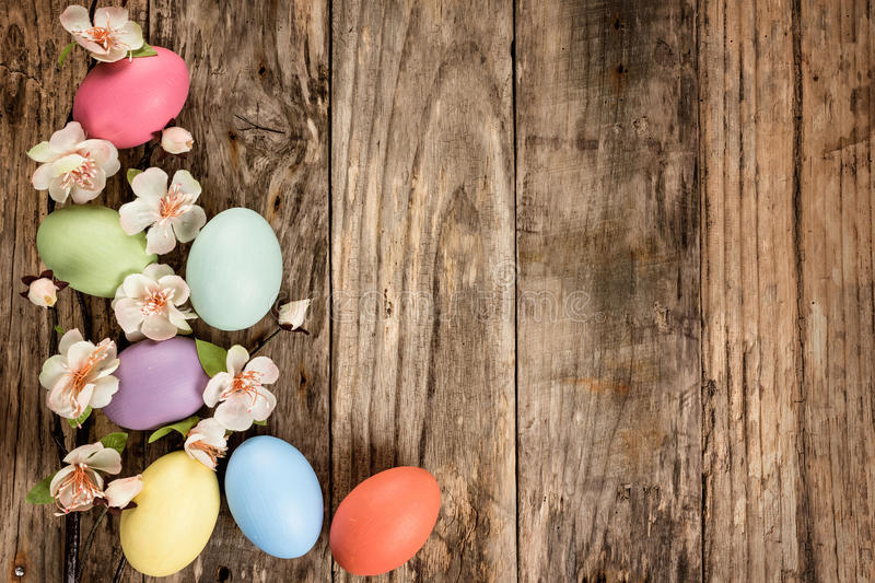 Easter background. Easter eggs and spring blossoms on the wooden background stock images
