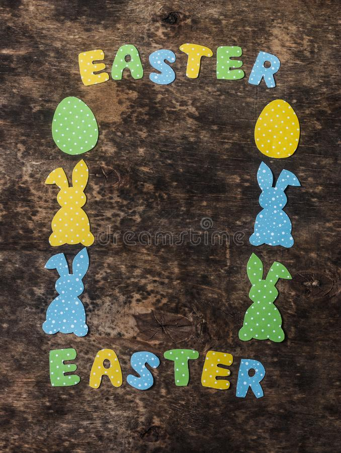 Easter background. Empty frame composition with paper handmade rabbits on wooden rustic background, top view. Easter decorations. royalty free stock photo