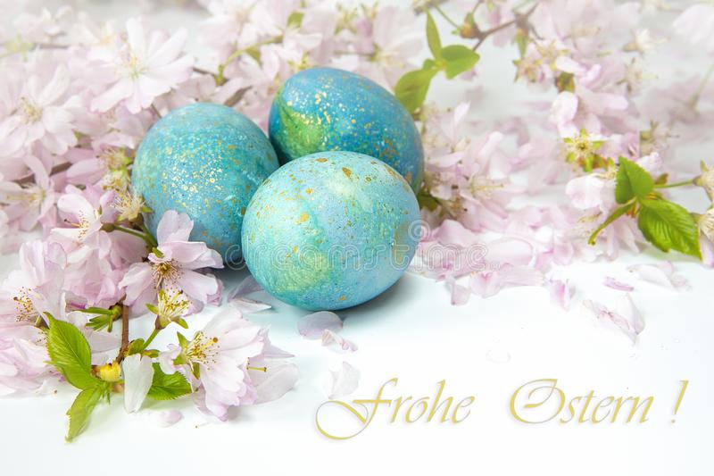Easter greetings in German `Happy Easter!`. Painted eggs with flowering twigs on a light background. Spring and holidays. Easter background. Family traditional stock images