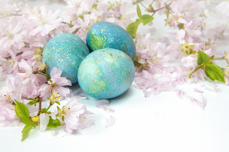 Easter background. Family traditional holidays. Painted eggs with flowering twigs on a light background. It`s spring. Easter eggs with flowering twigs .Spring stock photography