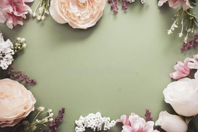 Easter background frame with flower composition on green board. Festive frame or border. Top view with copy space. Easter background with flower composition on stock photography