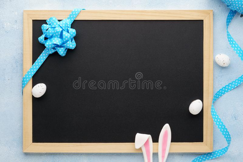 Easter background with funny bunny ears, chalkboard and ribbon. Easter background with funny bunny ears, chalkboard, eggs and blue ribbon. Holiday sale mockup stock photography