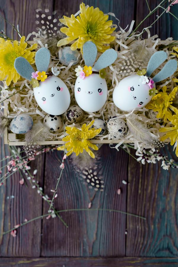 Easter background, homemade eggshell bunnies and yellow chrysanthemum in wooden box stock photo