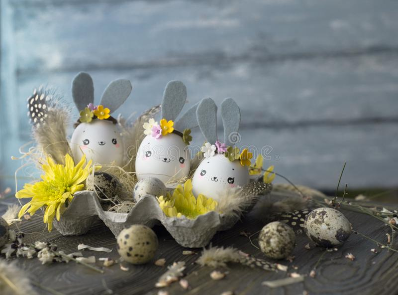 Easter background, homemade eggshells rabbits and yellow chrysanthemum in cardboard boxes royalty free stock photography