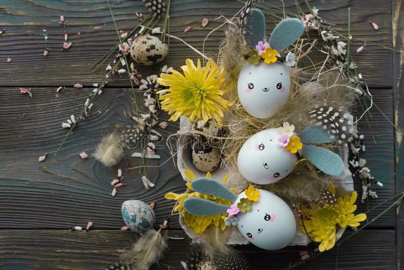 Easter background, homemade eggshells rabbits and yellow chrysanthemum in cardboard boxes royalty free stock images