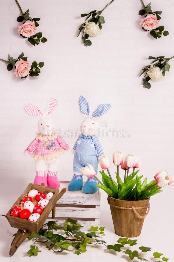 Easter background with pink and white tulips, toy bunnies and red eggs. royalty free stock photography