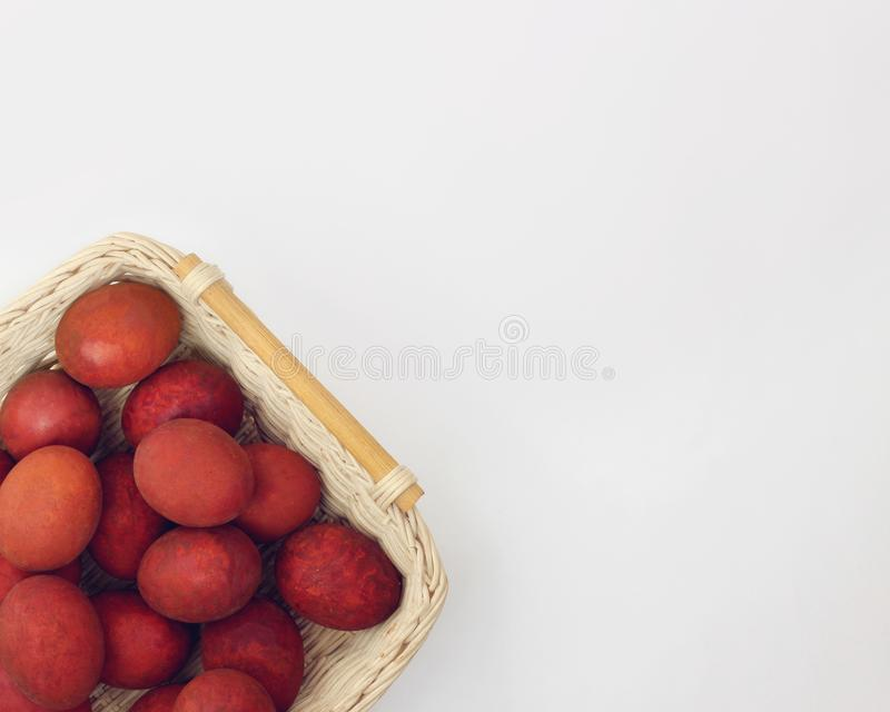 Easter background. Red eggs in basket on white background, top view royalty free stock photos