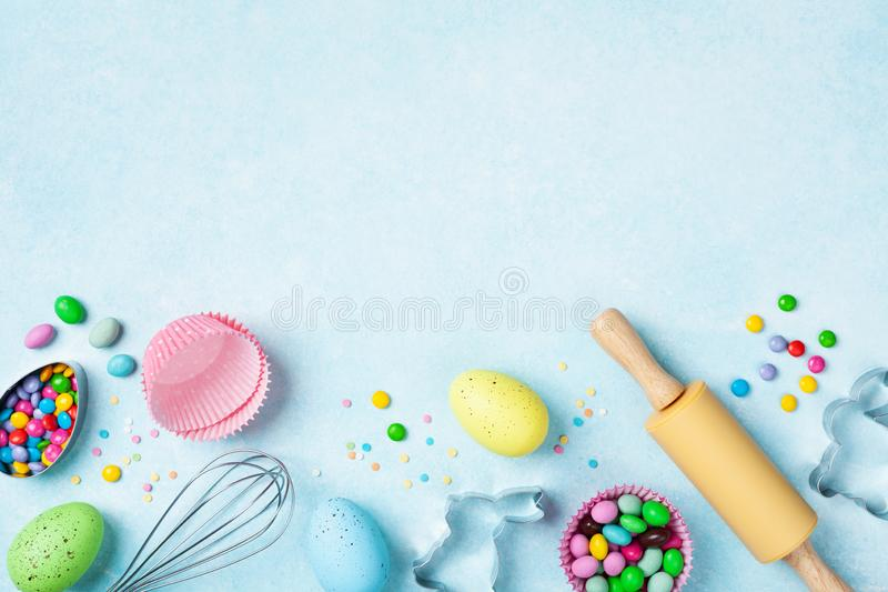 Easter baking background with rolling pin, whisk, decorative eggs, cookie cutters, candy and colorful confetti on kitchen table royalty free stock image