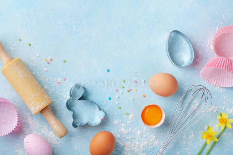 Easter baking background with rolling pin, whisk, eggs, flour and colorful confetti on blue table top view. Flat lay royalty free stock image