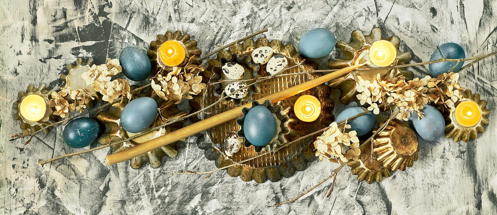 Easter banner: composition from blue eggs, cake forms, tree branches, dry flowers and candles on concrete background. Copy space, Christian religious festival stock images