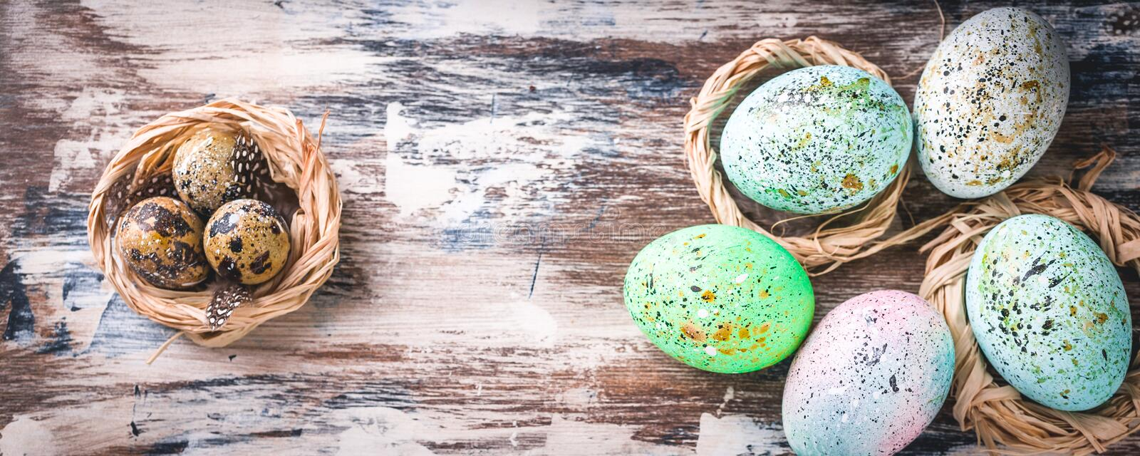 Easter banner. Easter eggs in nests. Rustic surface. Vertical shot royalty free stock photos