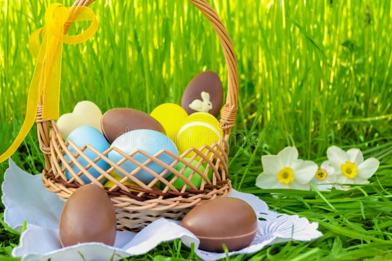 Easter basket with easter chocolate eggs and colored eggs on green grass background. stock image