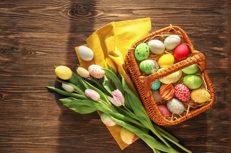 Easter basket with colorful eggs and spring flowers on wooden background, top view stock images