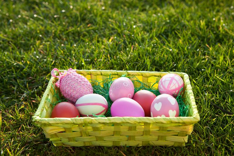 Easter basket with coloured Easter eggs on the lawn with space for additional text. stock photo