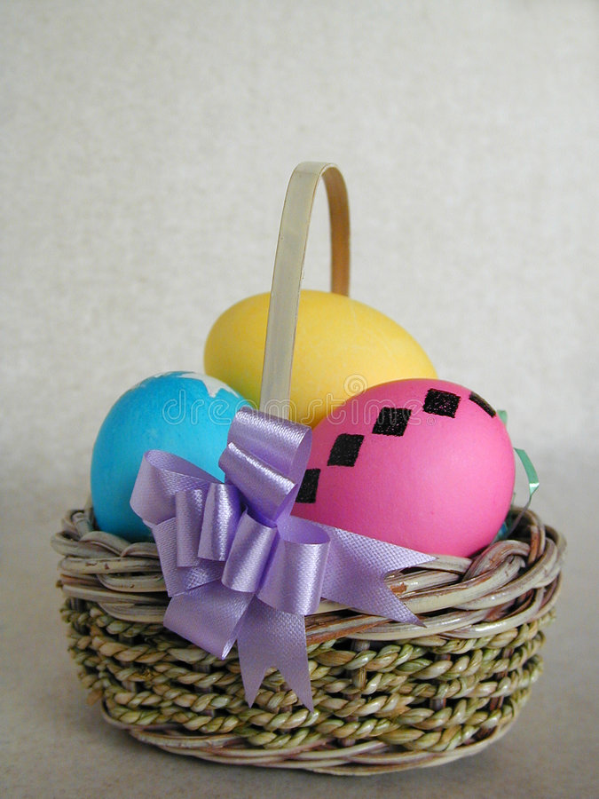 Easter Basket of Eggs. A small basket with yellow, pink, and blue easter eggs royalty free stock photography