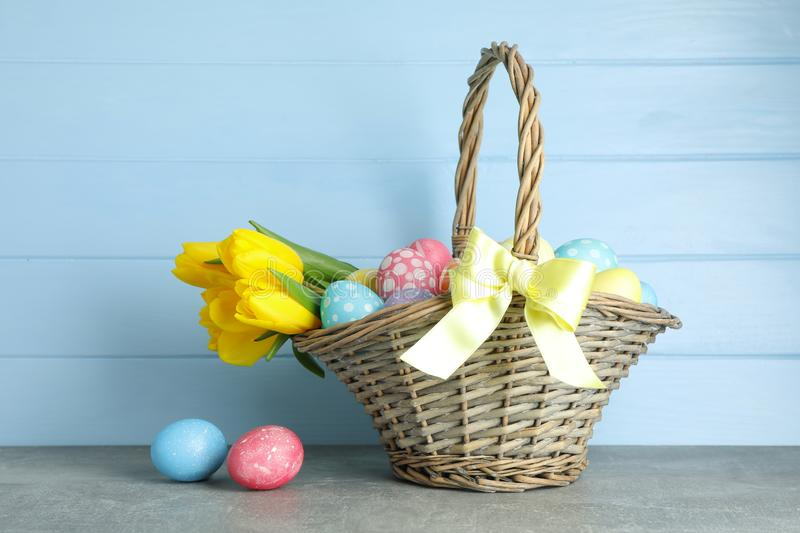 Easter basket filled with colorful eggs and flowers stock image