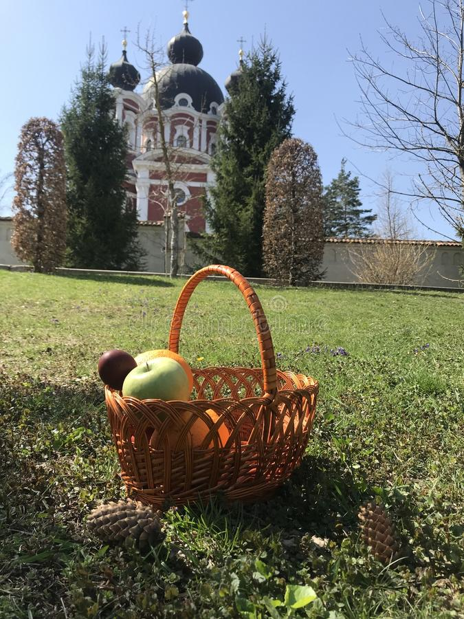 Easter basket with fruit and eggs on the grass stock photo