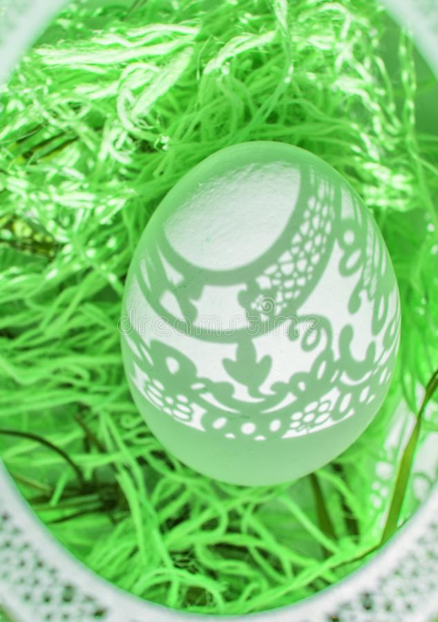 Easter. A beautiful Easter card with an openwork oval frame through which beautiful shadows fall on a white egg. Green background royalty free stock image