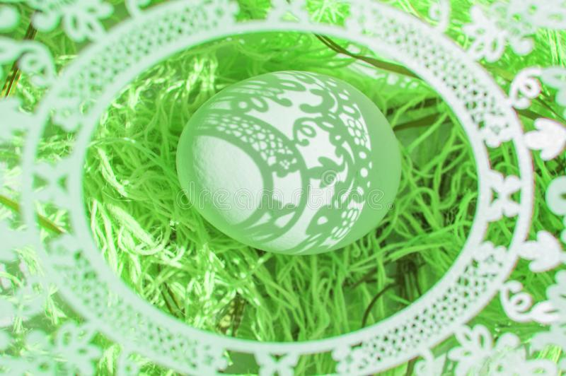Easter. A beautiful Easter card with an openwork oval frame through which beautiful shadows fall on a white egg. Green background stock photo
