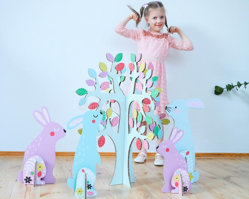 Easter 2019 Beautiful little girl in a dress with Easter decorations. Big Easter bunnies. A lot of different colorful royalty free stock image