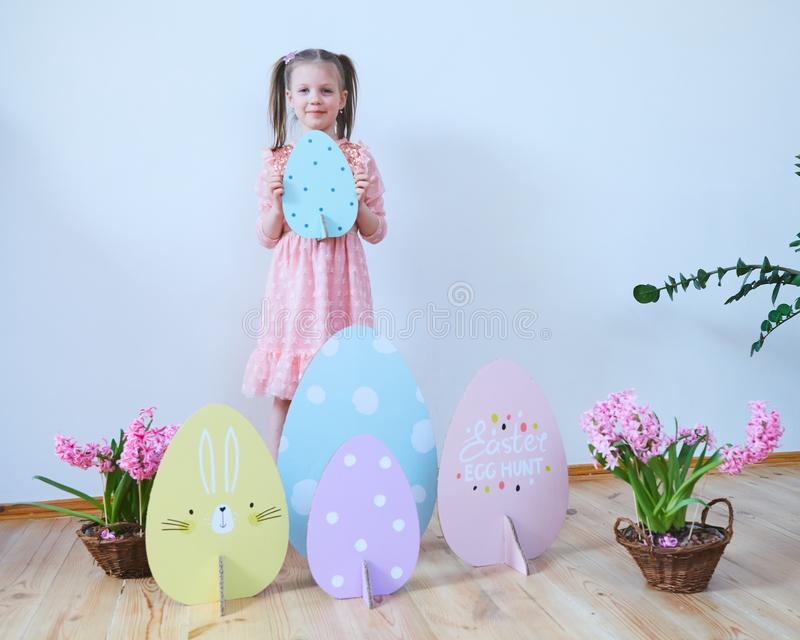 Easter 2019 Beautiful little girl in a dress with Easter decorations. Big Easter eggs and bunnies, colorful place. A lot stock photos