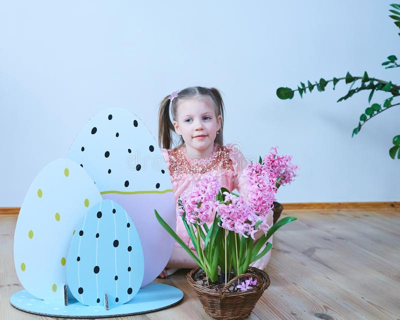 Easter 2019 Beautiful little girl in a dress with Easter decorations. Big Easter eggs and bunnies, colorful place. A lot royalty free stock photography