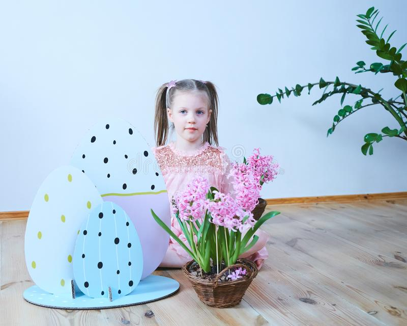 Easter 2019 Beautiful little girl in a dress with Easter decorations. Big Easter eggs and bunnies, colorful place. A lot stock image