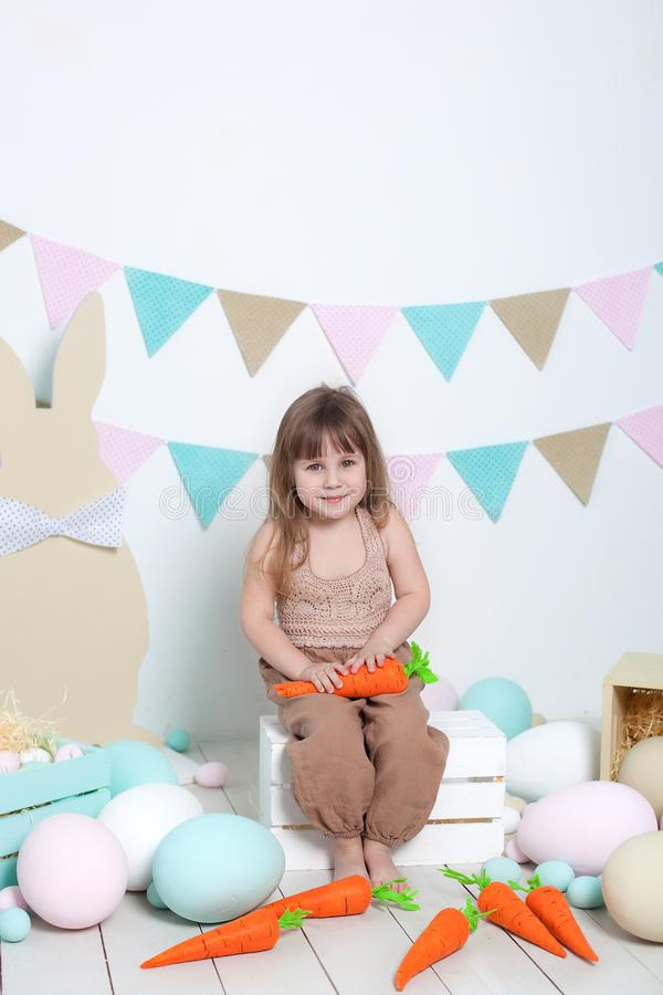 Easter! Beautiful little girl on a white background with carrot, colorful eggs, basket and hares. Easter location, Easter decorati stock image