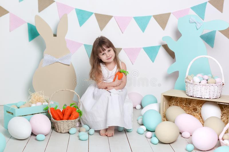 Easter! Beautiful little girl in a white dress with Easter eggs and a basket on a bright Easter scenery. Easter location, decorati stock images