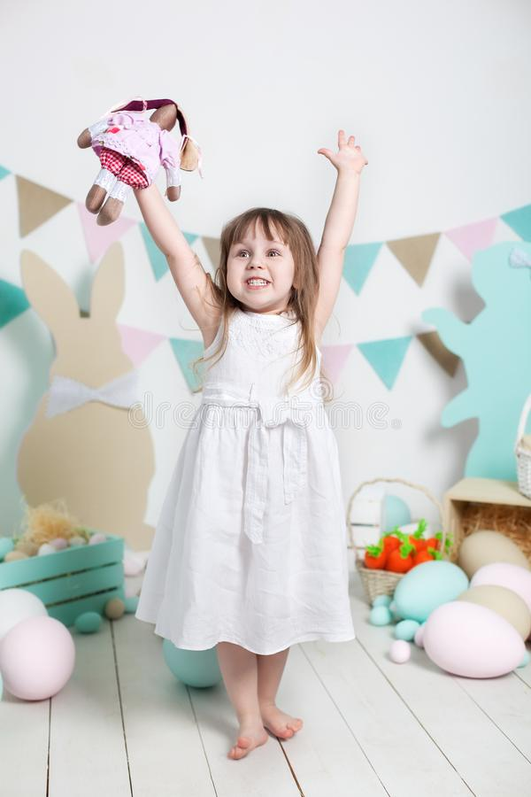 Easter! Beautiful little girl in a white dress rejoices at the holiday. Many different colorful Easter eggs, colorful interior. fa. Mily holidays. Easter bunny royalty free stock photo