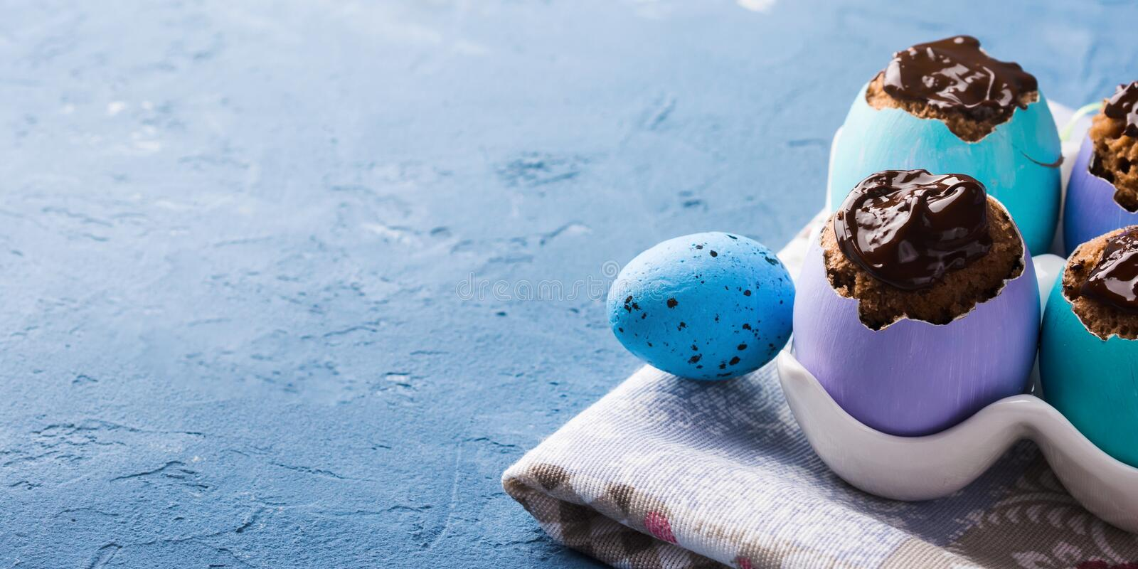 Easter background with cakes in eggs. Easter blue background with cakes in colorful egg shells stock photography