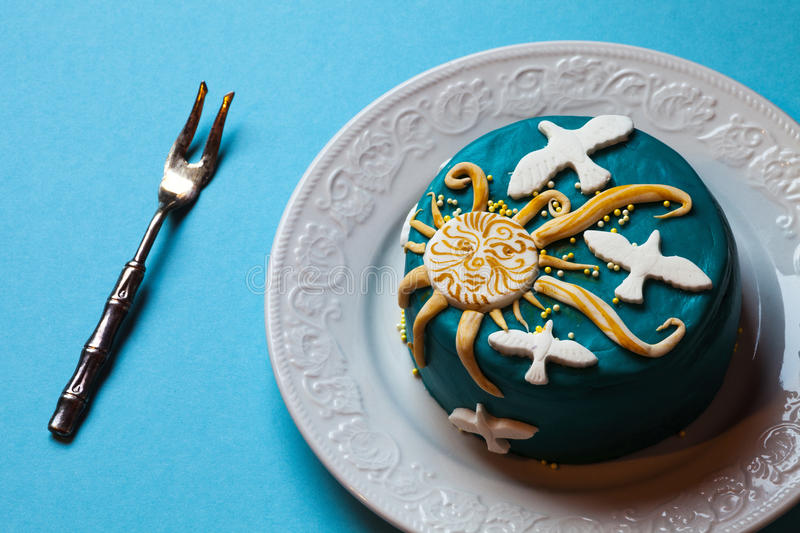 Easter blue cake, yellow sun and white doves in the white plate with fork. Blue background. stock photos