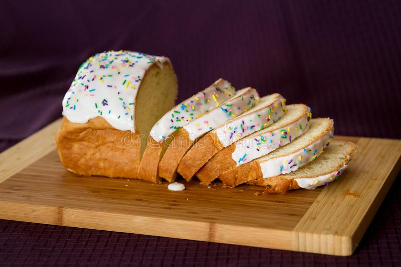 Paska loaf on a wooden cutting board covered in icing and sprinkles. Easter bread cut into slices royalty free stock photography