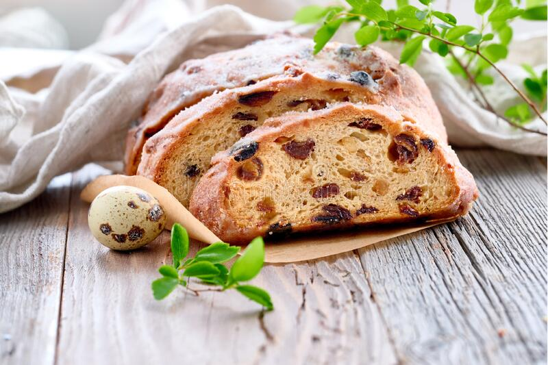 Easter bread, close-up on traditional fruty bread on rustic wood with fresh leaves and quail egg. Easter Bread (Osterbrot in German). Close-up on traditional royalty free stock photography