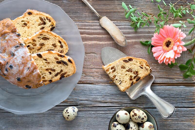 Easter Bread (Osterbrot in German). Top view of traditional fruty bread on rustic wood with fresh leaves and quail eggs. Traditional German dessert for Easter royalty free stock photos