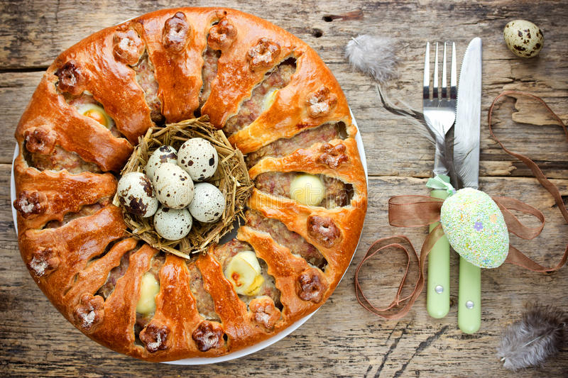 Easter bread ring stuffed with minced meat and quail eggs on old. Wooden table , Easter food in rustic style stock photo