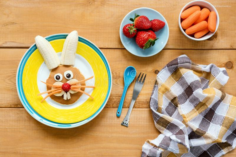 Easter breakfast for kids. Easter bunny shaped pancake with fruits royalty free stock images