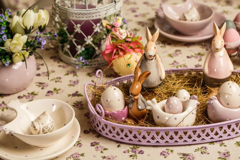 Easter breakfast table with tea,eggs in egg cups, spring flowers in vase and Easter decor. Easter composition stock images