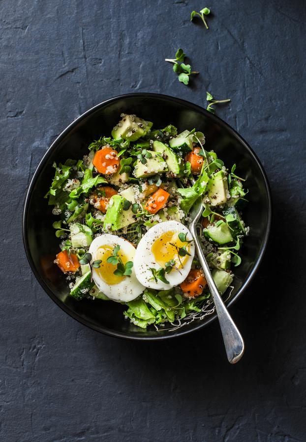 Easter brunch quinoa, eggs, avocado, cucumber, carrot salad on dark background, top. Healthy vegetarian food concept. Easter brunch quinoa, eggs, avocado royalty free stock images