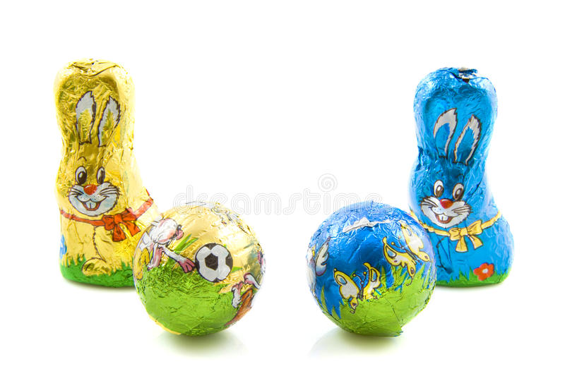 Easter bunnie. Two chocolate bunnies with two balls in foil isolated over white stock photos
