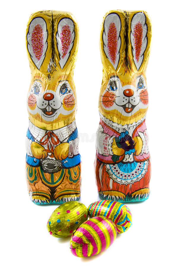 Easter bunnie. Chocolate easter bunnie in foil with chocolate eggs isolated over white royalty free stock photography