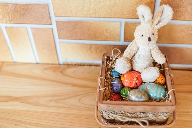 Easter bunny and colorful eggs in the basket on wood background. copy space. happy easter celebration card stock photography